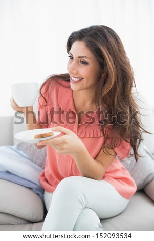 Pretty brunette sitting on her sofa holding cup and saucer at home in the sitting room - stock photo