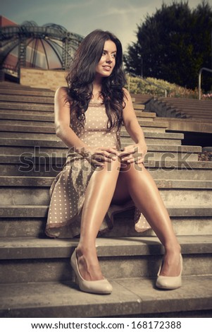 Pretty brunette sitting on park stairs