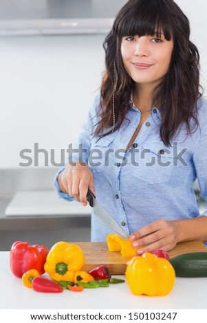 Pretty brunette slicing vegetables at kitchen counter