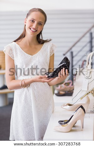 Pretty brunette smiling at camera and showing a heel shoe in shoe store - stock photo