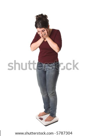 Pretty brunette standing on the scale with a shocked look on her face and her hands in front of her face - stock photo