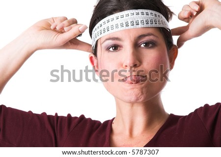 Pretty brunette sticking out her tongue and holding the measuring tape around her head in a protest against all diets