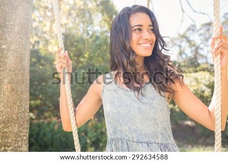 Pretty brunette swinging in park on a sunny day - stock photo