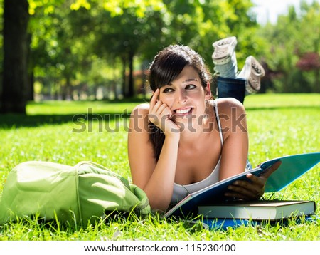 Pretty brunette teen studying and smiling in park.