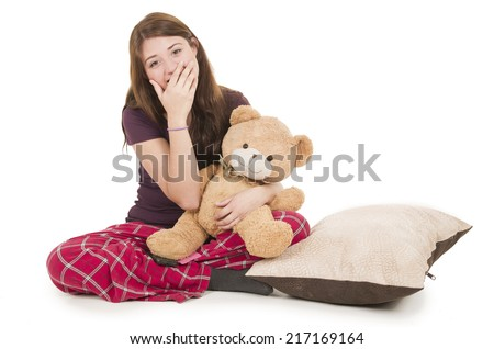 Pretty brunette teenage girl in pajamas pyjamas waking up huggin teddy bear isolated on white - stock photo