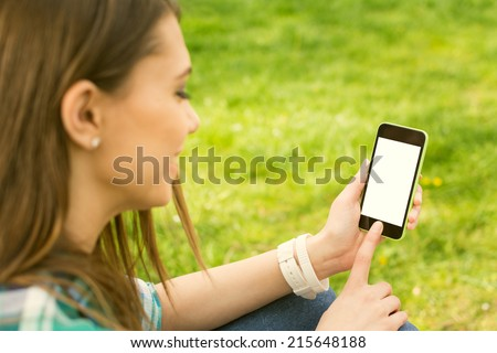 Pretty brunette teenage girl with smartphone outdoors in park. Closeup of female hands and smart phone with isolated white screen. Mock-up concept. - stock photo