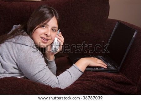 Pretty brunette teenage Hispanic girl laying on the sofa and typing on laptop and talking on a cordless phone