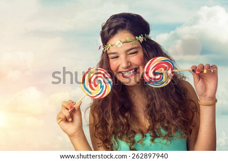 Pretty brunette teenager eager for her big and sweet lollipop - stock photo