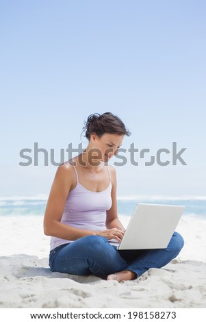 Pretty brunette using laptop on the beach on a sunny day