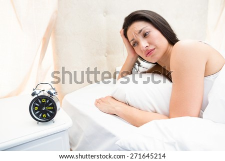 Pretty brunette waking up on bed at home - stock photo