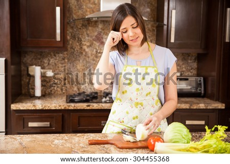 Pretty brunette wearing an apron cutting some onions in the kitchen and crying - stock photo