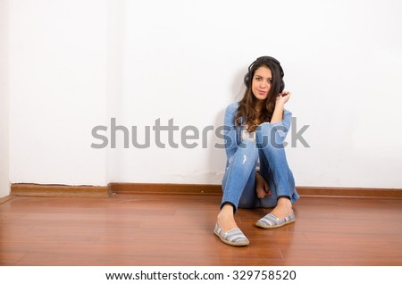 Pretty brunette wearing denim jeans and shirt plus white top sitting on wooden surface her back against wall, black headphones listening to music. - stock photo