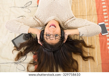 Pretty brunette wearing denim jeans white top lying down on bedsheets daydreaming with smartphone and tablet. - stock photo