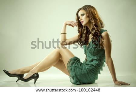 pretty brunette wearing green fashion dress on light background - stock photo
