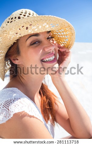 Pretty brunette wearing straw hat and looking at camera at the beach - stock photo