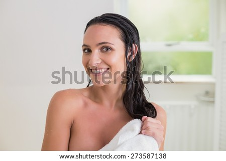 Pretty brunette wiping her hair with bath towel - stock photo