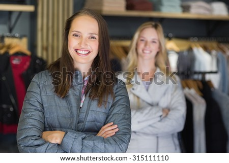 Pretty brunette with arms crossed looking at camera with friend behind in clothes store - stock photo