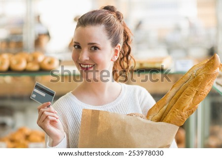 Pretty brunette with bag of bread and credit card at the bakery
