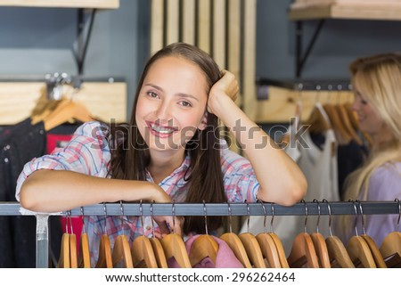 Pretty brunette with head on hand smiling at camera in clothes store