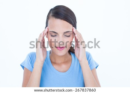Pretty brunette with headache touching her temples on white background - stock photo