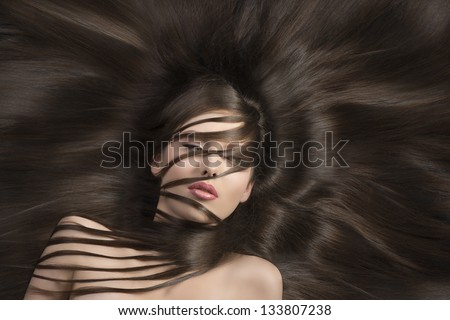 pretty brunette with long  hair laying down and some locks on the face and the neck - stock photo