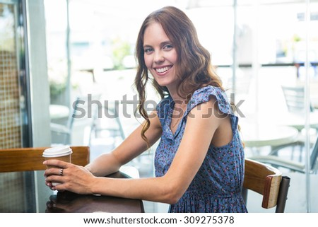 Pretty brunette with take away cup in a coffee shop