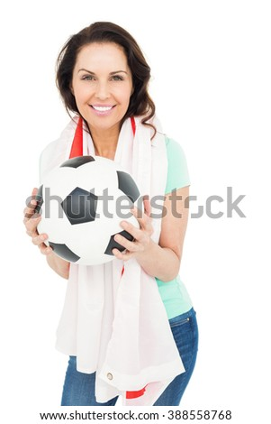 Pretty brunette with thumbs up holding soccer ball over white background - stock photo