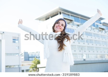 Pretty brunette with warm clothes raising hands outside