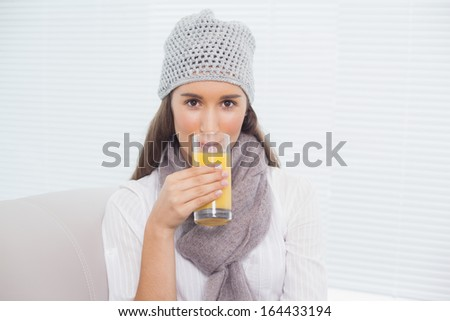 Pretty brunette with winter hat on drinking orange juice sitting on cosy sofa - stock photo