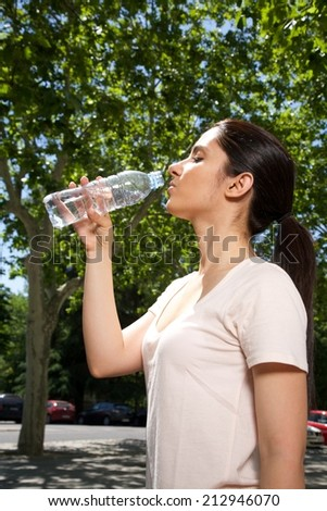 pretty brunette woman drinking water from plastic bottle  - stock photo