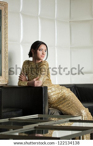 Pretty brunette woman in gold dress posing on sofa