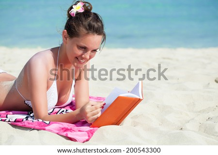 Pretty brunette woman is reading a book while lying on a beach - stock photo