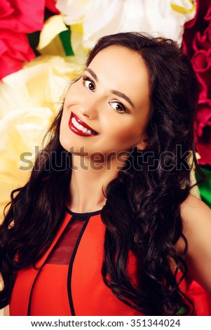 Pretty brunette woman looking at camera and smiling. Floral background. - stock photo