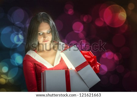 Pretty brunette woman opening the magic Christmas present box