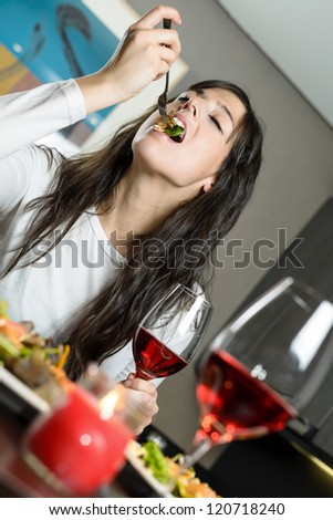 Pretty brunette woman sitting at the table eating a salad with a fork, while holding a glass of red wine. Romantic dinner for a couple with candle and drink. - stock photo