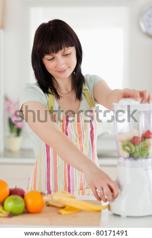 Pretty brunette woman using a mixer while standing in the kitchen