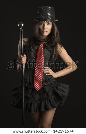 pretty brunette woman wearing like cabaret actress with black corset, red tie and hat taking stick in the hand on black background - stock photo