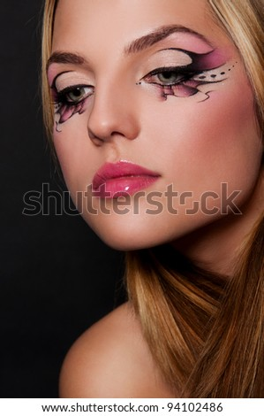 pretty brunette woman with creative makeup on black background - stock photo