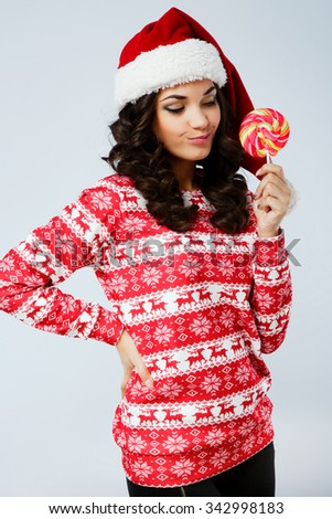 Pretty brunette woman, with curly hair, wearing in red Christmas sweater and santa hat, looking at colorful candy, on the white background, in studio, waist up