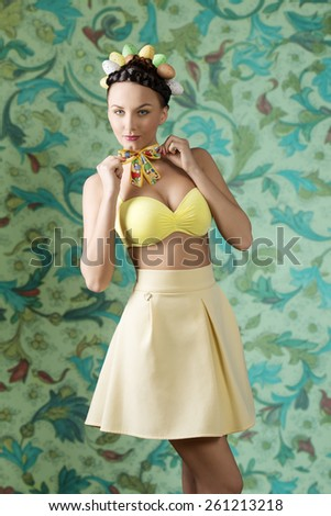 Pretty, brunette woman with funny hairstyle with colorful eggs. She wear yellow dress, bra and loop on her neck. - stock photo