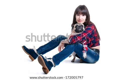 Pretty brunette woman with long straight hair, sitting and playing together with her friend pug dog pet, both wearing squared pattern shirts, both looking at camera. Isolated on white