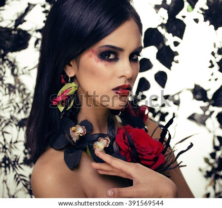 pretty brunette woman with rose jewelry, black and red, bright make up kike a vampire closeup red lips - stock photo