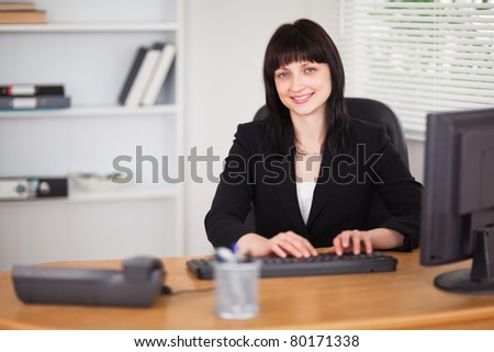 Pretty brunette woman working on a computer while sitting at a desk in the office