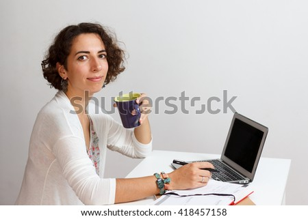 Pretty brunette woman working on laptop with notebook and cup of tea at home. Selective focus. White background