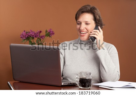 Pretty brunette working or shopping at a laptop on the kitchen table with a cup of coffee and a phone with purple  flowers in the background - stock photo