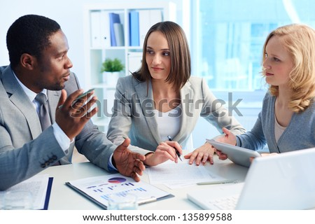 Pretty business interns listening to their team leader - stock photo