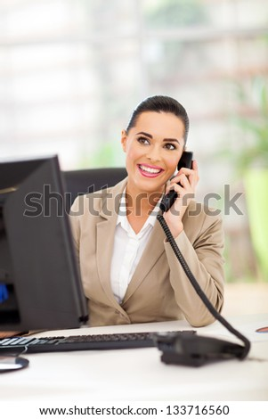 pretty business woman answering telephone in office