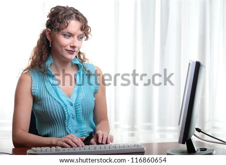 Pretty business woman at office desk - stock photo