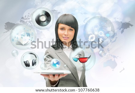Pretty business woman holding tablet computer and different objects are flying from touch screen - stock photo