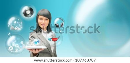 Pretty business woman holding tablet computer and different objects are flying from touch screen